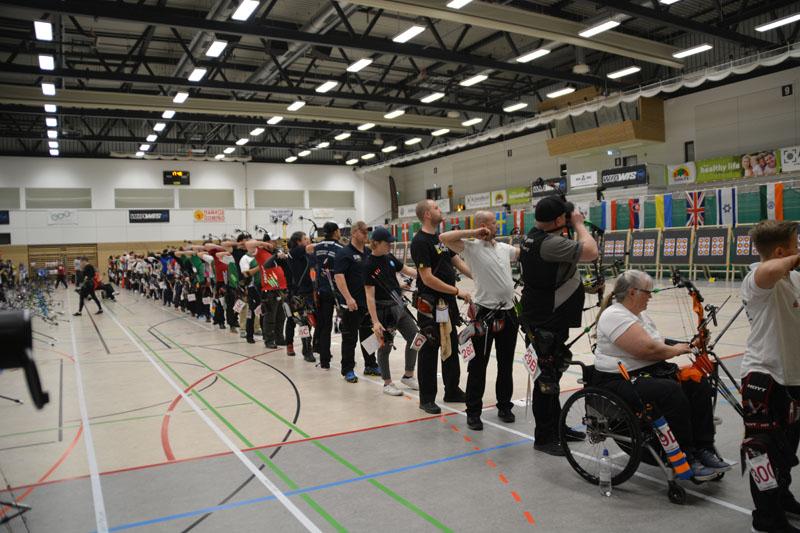 eine lange Reihe von Menschen mit und ohne Behinderungen an der Schießlinie beim Wettkampf.