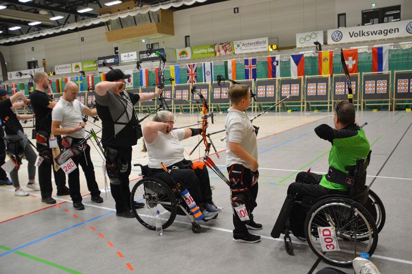 Eine Reihe von Para-Schützinnen und Para-Schtzen im Wettkampf. Ob Frau oder Mann, im Rollstuhl oder stehend, alle stehen bunt gemsicht nebeneinander.