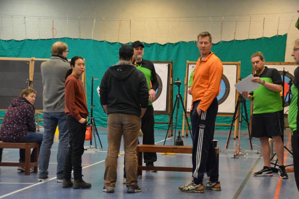 Eine Gruppe von Menschen beim Para-Bogebnschießen Workshop in einer Turnhalle.